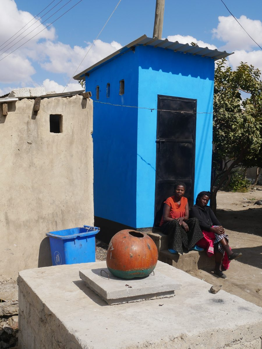 two women sit on the steps of their new blue latrine, next to the old one